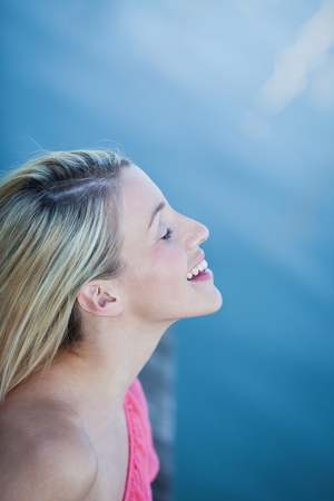 head tilted: Beautiful woman enjoying the sunshine laughing with her head tilted back to the warmth of the sun