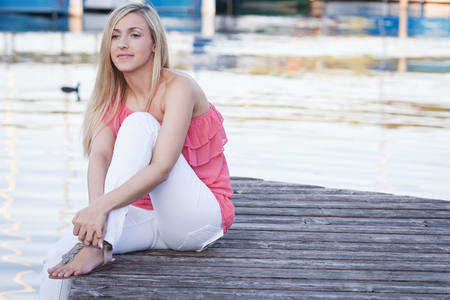 downcast: Beautiful young blond woman daydreaming sitting barefoot on a wooden jetty or deck outdoors in summer with downcast eyes and a faraway look as she reminisces