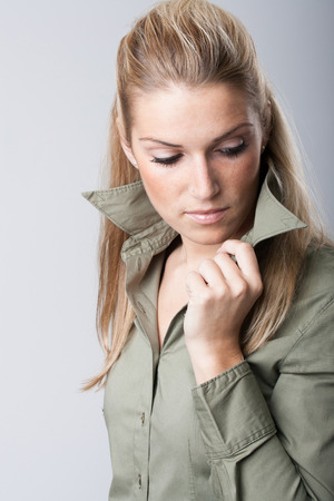 introspective: Introspective beautiful young woman standing thinking with her hand to her chin and downcast eyes Stock Photo
