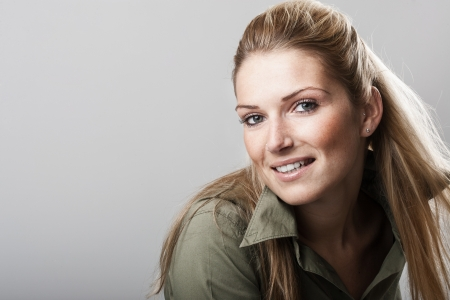 hair tied: Beautiful woman with long blond hair tied neatly back and a friendly smile looking at the camera, over grey with copyspace
