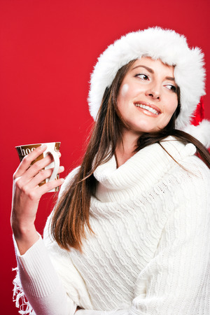 Happy woman wearing a Santa hat and holding a cup in a Christmas mood photo