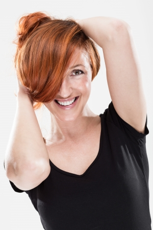 Very happy and smiling redhead woman with sexy expression while playing with her hair photo