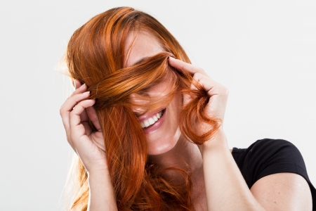 Playful and happy young redhead woman smiling and being shy covering her eyes with the hair photo