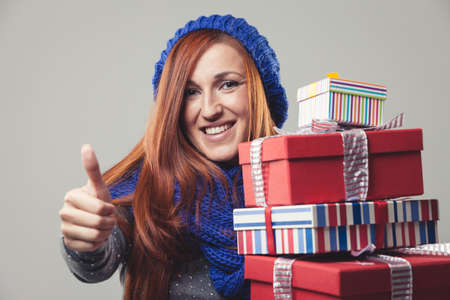 Happy woman holding a pile of Christmas gifts and giving thumbs-up in a positive mood photo