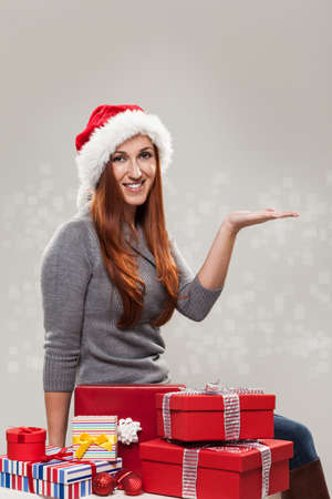 Young happy woman sitting next to Christmas gifts wearing a Santa hat with the hand in a holding object position photo