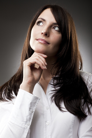 Thoughtful attractive woman with a serious expression standing staring up into the air with her hand to her chin