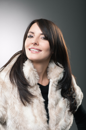 head tilted: Beautiful young woman with long straight brunette hair in a stylish fur jacket looking at the camera with her head tilted back and a friendly smile
