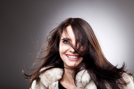 windblown: Tousled beautiful young woman with a carefree warm smile and long windblown hair, head and shoulders portrait on a grey background with highlight