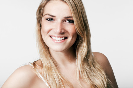 vivacious: Beautiful young blond woman with a vivacious smile beaming as she looks directly at the camera, close up head portrait on white
