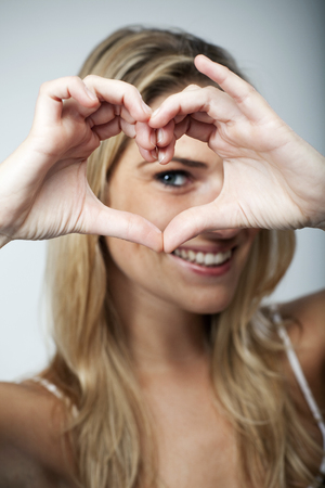 making love: Playful beautiful young blond woman making a heart gesture with her fingers to show her love and affection or that she likes something Stock Photo