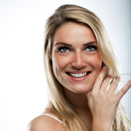 contentment: Gorgeous blond woman looking thoughtfully upwards with a happy smile of contentment on her face as she recalls happy memories Stock Photo