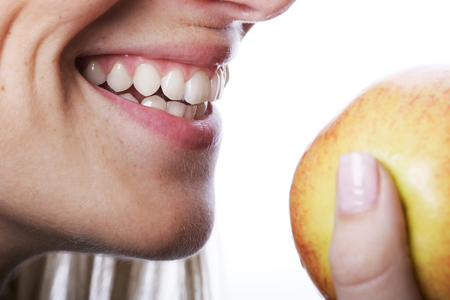 dentition: Smiling woman with beautiful teeth about to bite into a ripe juicy apple that she is holding in her hand, close up of her mouth isolated on white