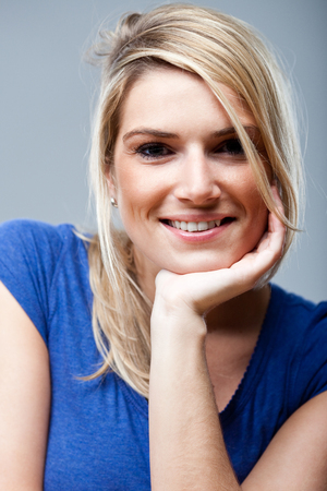 Natural beautiful young happy woman with a lovely smile and long blond hair tied back sitting with her chin resting o her hand smiling at the camera