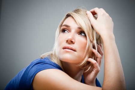 Wistful beautiful woman with a look of sad longing sitting daydreaming looking up into the air with a faraway expression Stock Photo