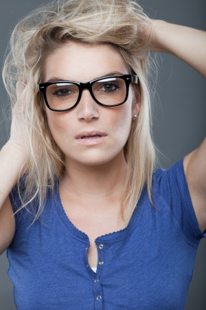 consternation: Concerned young woman in black rimmed spectacles gazing at the camera with a serious confounded expression and her hands raised to her dishevelled long blond hair