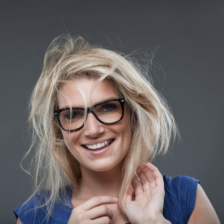 vivacious: Beautiful laughing young woman with a wild blond hairstyle wearing heavy rimmed glasses looking at the camera with a vivacious smile