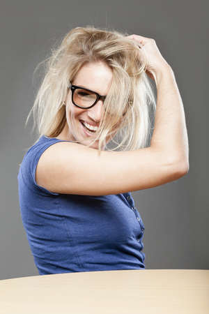 tousled: Crazy girl with a wild blond hairstyle, black rimmed glasses and a playful mischievous smile sitting at a table with her hand raised to her head