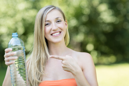 endorsing: Beautiful healthy young woman standing outdoors in a park or garden pointing to a bottle of fresh pure water with a vivacious smile Stock Photo