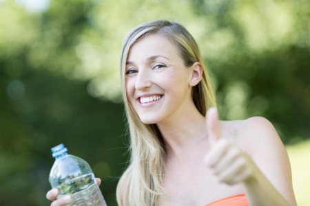 quencher: Smiling beautiful woman giving a thumbs up of approval for the bottle of fresh pure water that she is holding endorsing it as the thirst quencher of choice Stock Photo