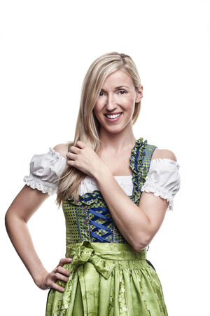 Bavarian beauty with long blond hair and a friendly smile wearing a traditional green dirndl, isolated on white photo