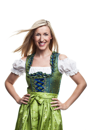Beautiful blond woman in a traditional dirndl standing smiling happily at the camera with her hans on her hips and her hair blowing in the breeze, isolated on white photo