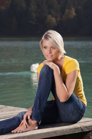 Beautiful carefree barefoot young woman with a short blond hairstyle enjoying a summer day at the lake sitting on a wooden jetty above the water photo