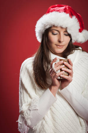 Woman holding and enjoying the aroma of a hot cup of cocoa drink wearing a Santa hat in a red background photo