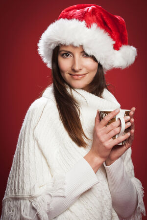 Happy woman holding a hot drink cup in Christmas wearing a warm shawl and a Santa hat in a red background photo