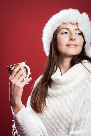 Pensive woman holding a cocoa cup and wearing a shawl and a Santa hat in a red background in a Christmas setting photo