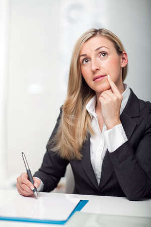 Thoughtful young businesswoman sitting at her desk writing notes looking up in contemplation with her finger to her chin Stock Photo