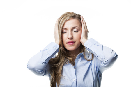 neuralgia: Woman with a migraine headache standing clasping her hands to her head with her eyes closed in pain, isolated on white