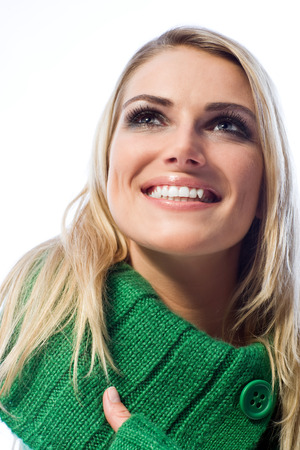 Low angle portrait of a happy woman with a big beaming toothy smile looking up thinking or daydreaming, on white