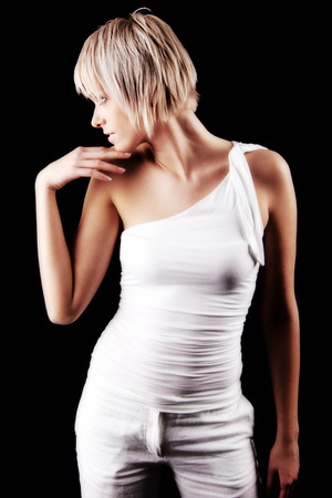 close fitting: Sexy modern young blond woman posing in a close fitting off the shoulder top looking sideways with her head in profile and hand to her chin on a dark background