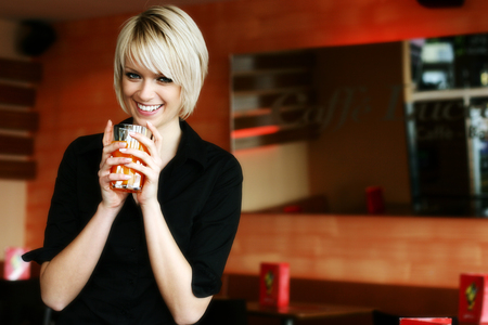 vivacious: Happy vivacious young blond woman drinking orange juice or cocktail cradling the glass in her hands as she glances down at the floor