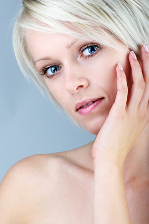 wistful: Beautiful gentle young blond woman with a wistful innocent look posing with her hand to her cheek, bare head and shoulders portrait on grey