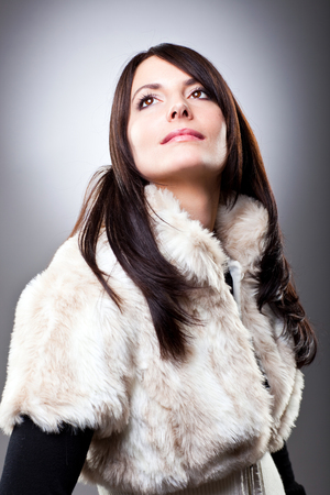 wistful: Wistful stylish young woman in a furry winter jacket staring up into the air with a look of longing , upper body portrait on a grey background