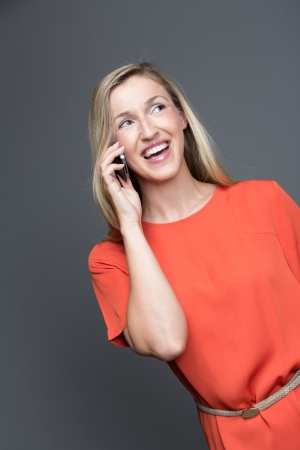 Laughing attractive young blond woman in a stylish orange top standing chatting on her mobile phone on a grey background Stock Photo - 23946423