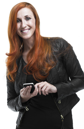 Attractive young redhead woman texting on her mobile looking up at the camera woth a warm friendly smile isolated on white photo