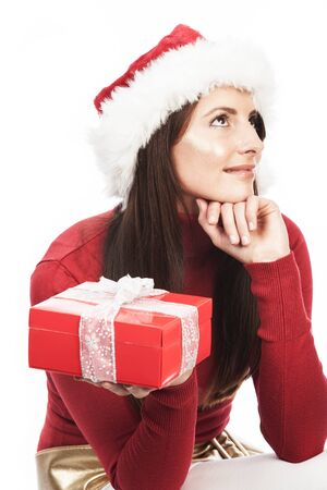 guessing: Woman guessing the contents of her Christmas gift in a decorative red box sitting with her chin on her hand looking upwards in contemplation, isolated on white Stock Photo