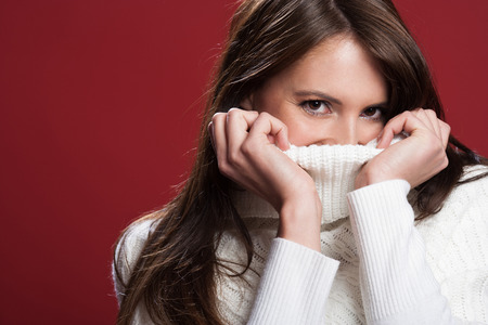 Attractive young brunette woman cuddling down into the warmth of the knitted wool collar her polo-neck jumper and peering at the camera with playful eyes