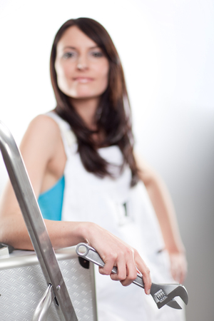 Attractive confident young woman in white dungarees holding a mole grip spanner leans on an aluminium stepladder, focus to the spanner Stock Photo - 23946456