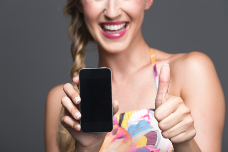 Smiling woman endorsing her smartphone giving a thumbs up gesture of approval as she displays the phone with the blank screen to the viewer, selective focus photo