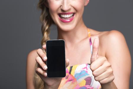 Sonriente mujer apoyando su teléfono inteligente con un pulgar hacia arriba gesto de aprobación mientras se muestra el teléfono con la pantalla en blanco para el espectador, atención selectiva