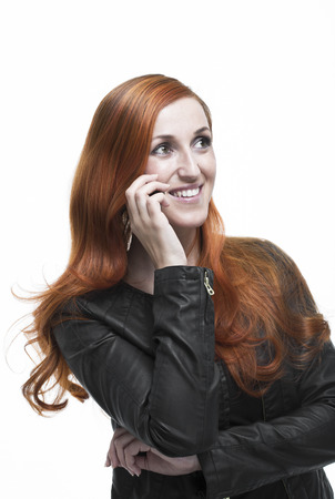 Attractive young redhead women in a trendy leather jacket standing chatting on her mobile phone and listening to the conversation with a smile, isolated on white photo
