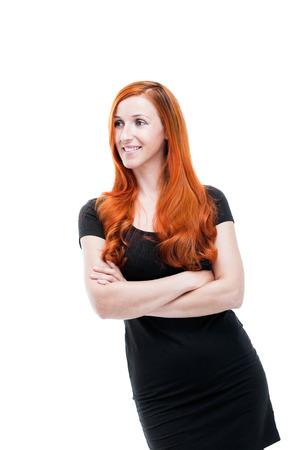 coppery: Modello attraente con i capelli rossi ramati in piedi con le braccia incrociate a guardare il lato e sorridente, isolated on white
