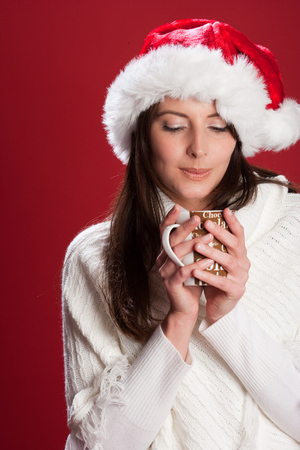 Beautiful young brunette Caucasian woman wearing a white sweater and Santas hat, enjoying a cup of hot chocolate, on red background photo