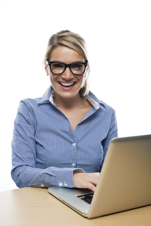 vivacious: Happy vivacious beautiful blond businesswoman wearing glasses working at her laptop laughing as she looks at the camera