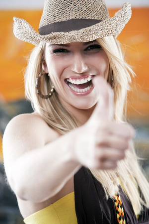 vivacious: Vivacious beautiful laughing young woman wearing a trendy straw hat giving a thumbs up gesture of approval with focus to her face