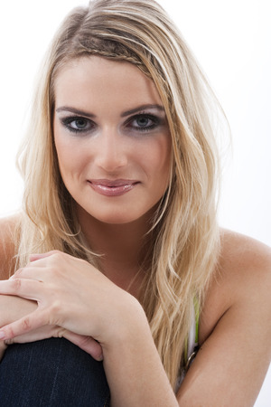 Attractive woman with long blond hair sitting looking directly into the camera with a smile, close up face portrait Stock Photo