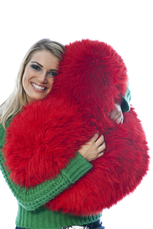 clutching: Gorgeous blond woman with a beaming smile of pleasure clutching a red heart shaped fluffy cushion in a tender depiction of love on Valentines Day, isolated on white